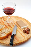 Pate, bread, glass of red wine, hazelnuts and knife on wood plat Stock Images