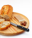 Pate, bread, hazelnuts and knife on wood plate Stock Photos