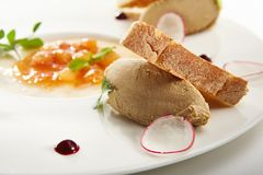 Specialties of the luxury restaurant. Pate of fowl with toast and citrus jam with radish slices and fresh herbs on flat white plate. Gastronomic restaurant menu Stock Photo
