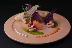 Pate med sås, rostat bröd, gelé och arugula på en platta, closeup Svart bakgrund Molekylär kokkonst Arkivbilder