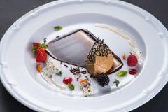 Patekött dekoreras med bär och svart choklad Pate av foiegras Läckerhet på en vit platta Restaurang arkivbild