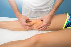 Patella mobilization by a professional physiotherapist.  royalty free stock photography