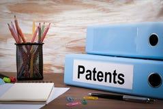 Patent kontorslimbindning på träskrivbordet På tabellen färgade blyertspennor, penna, anteckningsbokpapper Royaltyfri Foto