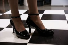 Patent-leather shoes. Beautiful legs in black patent-leather shoes on chess-checked floor Stock Images