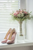 Patent pointed old pink pumps with matching flower bouquet Stock Photos
