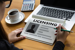 Patente la mano del hombre de negocios de la AUTORIZACIÓN del contrato de licencia que trabaja o fotografía de archivo libre de regalías