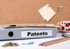 patente Ordner auf Schreibtisch Geld, Kaffeetasse und farbiges pencilsr Stockfoto