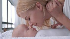 Paternidad apacible, juego joven de la madre con su pequeño bebé que miente en cierre cambiante de la tabla para arriba almacen de metraje de vídeo