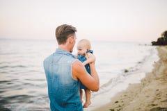 Paternidad feliz del tema Hombre cauc?sico joven del padre solo que detiene a un ni?o cualquier ni?o de la hija que comienza a ca foto de archivo libre de regalías