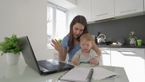 Paternidade dura, mamãe a multitarefas com grito pouco menino da criança ao trabalhar no laptop e ao falar sobre vídeos de arquivo