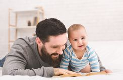 Father reading book to little baby son. Paternity leave activity. Daddy reading fairy tale to adorable little son, lying on bed together stock photos