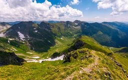 Path along the mountain ridge with snow on hills. Gorgeous summer scenery in Fagaras mountains of Romania Royalty Free Stock Photo