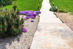 Path through alpine garden and sloped lawn. On backyard of country house Royalty Free Stock Photo