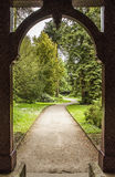 Path through arch leading to formal gardens Stock Photography