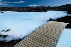 Path arround geothermal lake. Geothermal lake in lava field filled with turquoise water Royalty Free Stock Photography