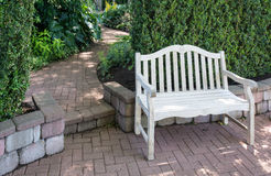 Path and bench. A whitewashed bench sits near a brick walkway as it winds into the distance Stock Photography