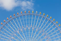 Path of big funfair ferris wheel against blue sky. Background Royalty Free Stock Images