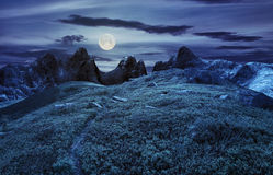 Path through boulders on hillside at night. Composite landscape with path through hillside meadow with white sharp boulders near cgi mountain peaks at night in royalty free stock image