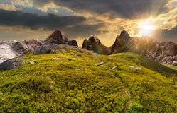 Path through boulders on hillside at sunset. Composite landscape with path through hillside meadow with white sharp boulders near cgi mountain peaks in sunset royalty free stock photos