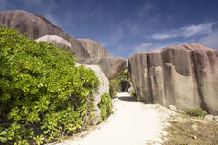 Path between boulders rocks La Digue island Seychelles, vacation background. Seychelles is the most beautiful tropical islands of the world's in the Indian Ocean Royalty Free Stock Image