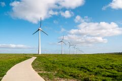 Free Path By The Dike To The Huge Windmill Park With Huge Turbines In The Netherlands Noordoostpolder, Green Energy Wind Mill Royalty Free Stock Images - 186317729