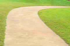 Path curving through green grass in golf course. Stock Photos