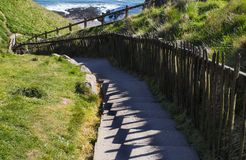 Path down in mountains, shadow of handrails,stairs,turning to. Path down in mountains, shadow of handrails,stairs, turning to the right stock image