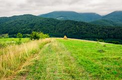 Path down the rural field on hillside. Lovely countryside scenery with haystack and forested mountains Stock Photo