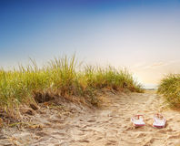 Path through dunes to beach. Flip flops on the sandy boardwalk over the dunes Royalty Free Stock Photography