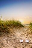 Path through dunes to beach. Flip flops on the sandy boardwalk over the dunes Stock Photo
