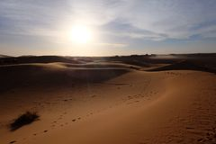 Path entrance and shadow of Sahara Desert with blue white cloud. Saharan, sandy near the village of Merzouga in Morocco. The sand dunes of Erg Chebbi in the Royalty Free Stock Image