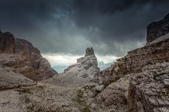 Path at foot of dolomitic pinnacle in a dark and cloudy mountain scenery. Dolomites, Cortina d`Ampezzo, Italy royalty free stock photo