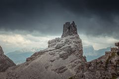 Path at foot of dolomitic pinnacle in a dark and cloudy mountain scenery. Dolomites, Cortina d`Ampezzo, Italy royalty free stock photography