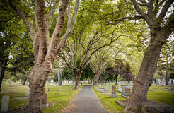 Path through forested graves, Ross Bay Cemetery, Victoria, BC Stock Photography
