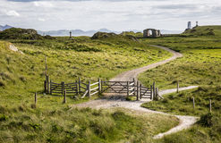 Path and gates on Ynys Llanddwyn, Anglesey, Wales, UK. Path leading through gates on Ynys Llanddwyn, Newborough, Anglesey, Wales, UK leading to lighthouse with Stock Image