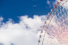 Path of Giant funfair ferris wheel against blue sky. Background Stock Photos