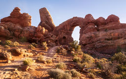 The path going to Turret Arch in Arches National Park close to s. The sun is shining on the path going towards the unusual rock formation called the Turret Arch royalty free stock photos