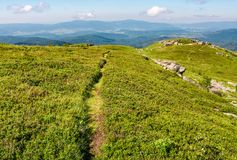 Path through grassy meadow to huge boulders. Beautiful mountainous landscape on summer morning Royalty Free Stock Image