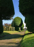 Path through graveyard. Pathway receding past landscaped bushes and hedges in graveyard Royalty Free Stock Photos