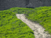 Path among the green mountains near fortress Stock Photo