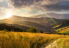 Path on hillside meadow in mountain at sunset Stock Images