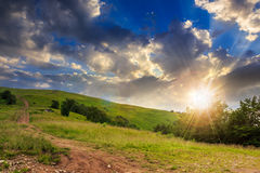 Path on hillside meadow in mountain at sunset Royalty Free Stock Image