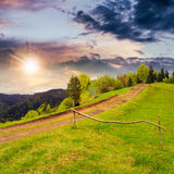 Path on hillside meadow in mountain at sunset Royalty Free Stock Photography