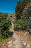 Path and huts made of stone under sunny blue sky, in the Village of Bories, near Gordes. Royalty Free Stock Images
