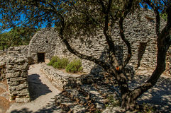Path and huts made of stone under sunny blue sky, in the Village of Bories, near Gordes.
