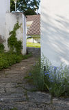 The path laid out by stones which goes near the plastered white Stock Photography