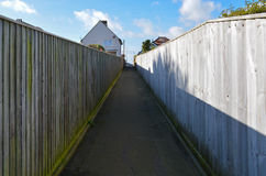 Path and Leading lines. A path between two wooden fences creates perspective and parallel lines leading towards houses in the background, with cloudy blue skies Royalty Free Stock Photo