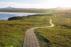 Path leading into sunset. A cobbled footpath along a seaside cliff walking into the sunset stock images