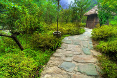Path leading to small hut. A narrow stone path leads to a tiny hut/shelter in the woods Royalty Free Stock Photography