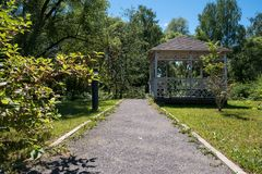 Path leading to wooden summerhouse standing among green trees. Path leading to wooden summerhouse standing among lush green trees and shrubs on bright sunny royalty free stock image